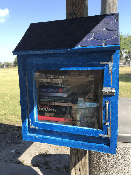 A small blue container with a window holding books